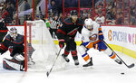 Carolina Hurricanes goalie Curtis McElhinney and Jaccob Slavin (74) defend against New York Islanders' Jordan Eberle (7) during the second period of Game 4 of an NHL hockey second-round playoff series in Raleigh, N.C., Friday, May 3, 2019. (AP Photo/Gerry Broome)