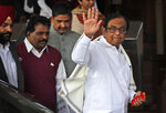 Indian lawmaker and former Finance Minister Palaniappan Chidambaram waves as he arrives at the Parliament House for a protest against the rise in onion prices, in New Delhi, India, Thursday, Dec. 5, 2019. Chidambaram, just released on bail in a bribery case, has joined a protest of the government's economic policies, which are being blamed for India's slowest economic growth in six years. (AP Photo/Manish Swarup)
