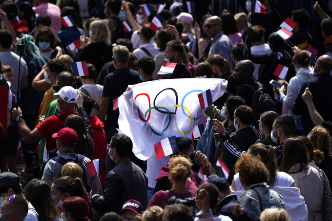 Fans carry a flag in the Olympics fan zone at Trocadero Gardens in front of the Eiffel Tower in Paris, Sunday, Aug. 8, 2021. A giant flag will be unfurled on the Eiffel Tower in Paris Sunday as part of the handover ceremony of Tokyo 2020 to Paris 2024, as Paris will be the next Summer Games host in 2024. The passing of the hosting baton will be split between the Olympic Stadium in Tokyo and a public party and concert in Paris. (AP Photo/Francois Mori)