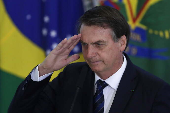 Brazil's President Jair Bolsonaro salutes during the swearing-in ceremony for the newly-named Secretary of Government, Army General Luiz Eduardo Ramos, at the Planalto Presidential Palace, in Brasilia, Brazil, Thursday, July 4, 2019. (AP Photo/Eraldo Peres)