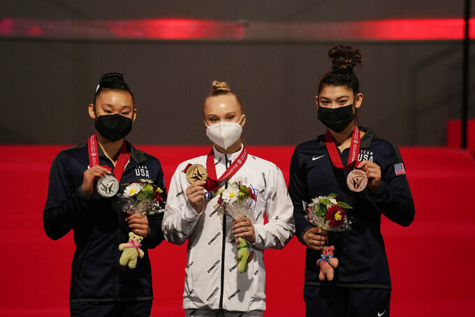 Angelina Melnikova, center, of Russia, with her gold medal, Leanne Wong, left, of the U.S., with her silver medal, and Kayla DiCello, of the U.S., with her bronze medal, pose for a photo during the victory ceremony after the women's all-around finals in the FIG Artistic Gymnastics World Championships in Kitakyushu, western Japan, Thursday, Oct. 21, 2021. (AP Photo/Hiro Komae)