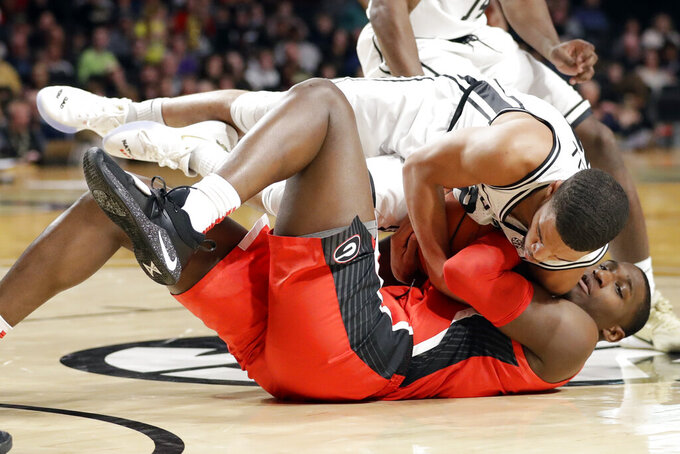 Vanderbilt's Jon Jossell, top, battles for the ball with Georgia's Mike Peake, bottom in the first half of an NCAA college basketball game Saturday, Feb. 22, 2020, in Nashville, Tenn. (AP Photo/Mark Humphrey)