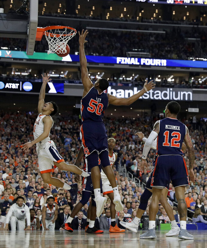 Virginia's Kihei Clark (0) goes up for a shot against Auburn's Austin Wiley (50) during the second half in the semifinals of the Final Four NCAA college basketball tournament, Saturday, April 6, 2019, in Minneapolis. (AP Photo/David J. Phillip)