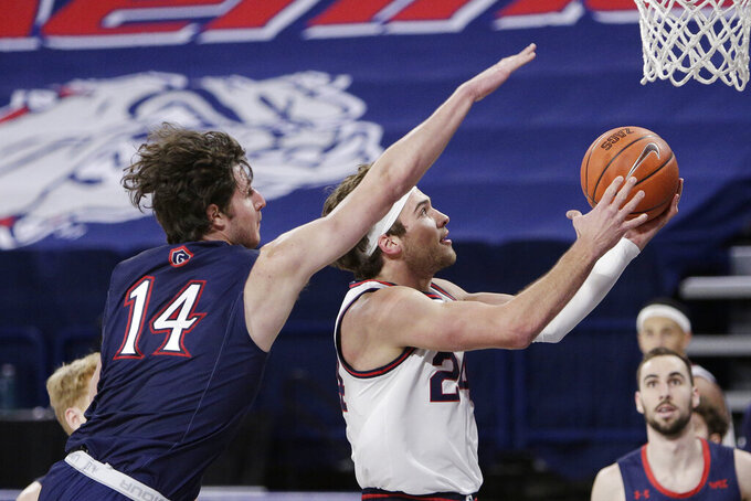 Gonzaga forward Corey Kispert, right, shoots in front of Saint Mary's forward Kyle Bowen during the first half of an NCAA college basketball game in Spokane, Wash., Thursday, Feb. 18, 2021. (AP Photo/Young Kwak)