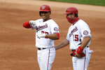Washington Nationals' Juan Soto, left, reacts at first after his single during the second inning of a baseball game against the New York Mets, Sunday, Sept. 27, 2020, in Washington. Nationals first base coach Bob Henley, right, looks on. (AP Photo/Nick Wass)