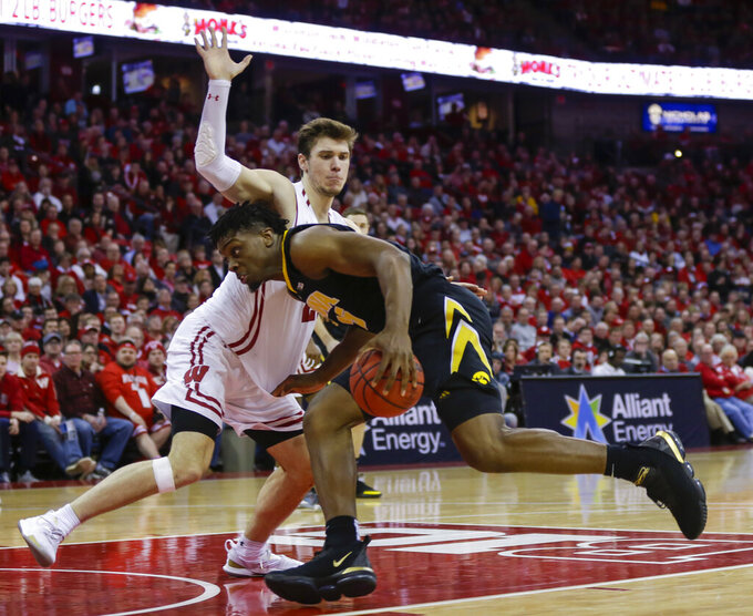Iowa's Tyler Cook (25) drives against Wisconsin's Ethan Happ during the first half of an NCAA college basketball game Thursday, March 7, 2019, in Madison, Wis. (AP Photo/Andy Manis)