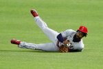Los Angeles Angels' Brian Goodwin falls to the ground after fielding a sacrifice fly by Texas Rangers' Robinson Chirinos in the second inning of a baseball game in Arlington, Texas, Friday, Aug. 7, 2020. The Rangers' Willie Calhoun scored on the play. (AP Photo/Tony Gutierrez)