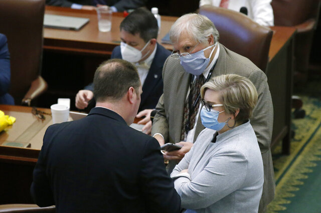 House floor leader Rep. Jon Echols, left, R-Oklahoma City, speaks with House Minority Leader Rep. Emily Virgin, right, D-Norman, and Rep. David Perryman, rear, D-Chickasha, Friday, May 22, 2020, in Oklahoma City. The Oklahoma Legislature approved a resolution that calls for sweeping powers granted to Oklahoma Gov. Kevin Stitt under a health emergency to expire at the end of the month. The Republican-controlled Legislature also voted to override Stitt's veto of several bills. (AP Photo/Sue Ogrocki)
