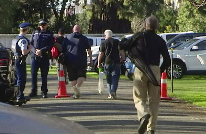 In this image made from video, people bring their guns to exchange for money in Christchurch, New Zealand Saturday, July 13, 2019. Dozens of Christchurch gun owners on Saturday handed over their weapons in exchange for money, in the first of more than 250 planned buyback events around New Zealand after the government outlawed many types of semi-automatics. (TVNZ via AP)