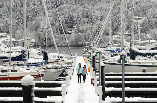 Abbie Brown and Mallory Burns stroll along the snow-covered dock at the Poulsbo Marina in Poulsbo, Wash., Monday, Jan. 13, 2020. (Meegan M. Reid/Kitsap Sun via AP)
