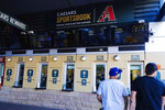 The general public get in line as the Arizona Diamondbacks partner with Caesars Entertainment setting up temporary sports betting windows at the Diamondbacks' Chase Field, the baseball home of the Diamondbacks baseball team, Thursday, Sept. 9, 2021, in Phoenix. The on-site sports betting permanent home just outside Chase Field will be opened in the coming months. (AP Photo/Ross D. Franklin)