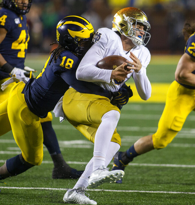 Michigan defensive lineman Luiji Vilain (18) tackles Notre Dame quarterback Phil Jurkovec, right, in the fourth quarter of an NCAA college football game in Ann Arbor, Mich., Saturday, Oct. 26, 2019. Michigan won 45-14. (AP Photo/Tony Ding)