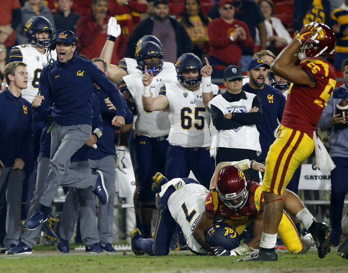 CAPTION CORRECTION: CORRECTS GAME ACTION: California head coach Justin Wilcox, left, leaps to celebrate what he thought was a first down by quarterback Chase Garbers, center, tackled by Southern California safety Marvell Tell III, second from right, as linebacker Jordan Iosefa, right, laments, but after a video replay it was determined not a first down during the second half of an NCAA college football game in Los Angeles, Saturday, Nov. 10, 2018. Instead, California ran on fourth-and-one for a first down and won 15-14. (AP Photo/Alex Gallardo)