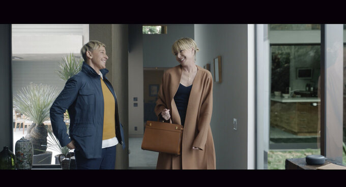 This undated image provided by Amazon shows Ellen DeGeneres, left, and her wife Portia De Rossi in a scene from the company's 2020 Super Bowl NFL football spot. Amazon will once again tout its Alexa voice assistant ad in a 90-second ad starring talk show host Ellen DeGeneres and her wife actress Portia de Rossi as they imagine what people did before they could ask Alexa to perform tasks. (Amazon via AP)