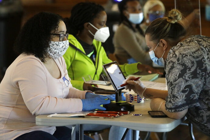 Poll worker Neuza Ferreira, left, checks in voter Christina Tremblay, right, both of Providence, R.I., Tuesday, June 2, 2020, at a voting station, in Providence. In-person voting is being offered at a reduced number of locations for voters who missed the deadline to request a mail ballot. (AP Photo/Steven Senne)
