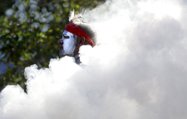 Russell Dawson of the Koomurri Aboriginal Dancers participates in a smoking ceremony during Australia Day ceremonies in Sydney, Tuesday, Jan. 26, 2021. (AP Photo/Rick Rycroft)