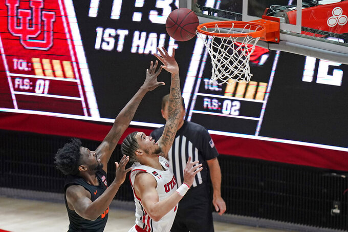Oregon State guard Tariq Silver, left, defends against Utah forward Timmy Allen during the first half of an NCAA college basketball game Wednesday, March 3, 2021, in Salt Lake City. (AP Photo/Rick Bowmer)