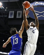 Xavier's Tyrique Jones (0) reaches for a rebound next to Creighton's Christian Bishop (13) during the first half of an NCAA college basketball game Wednesday, Feb. 13, 2019, in Cincinnati. (AP Photo/John Minchillo)