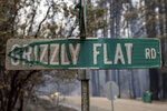 FILE - In this Tuesday, Aug. 17, 2021 file photo, a partially melted street sign stands after the Caldor Fire burned through Grizzly Flats, Calif. Last week, managers overseeing the fight against the massive wildfire scorching California's Lake Tahoe region thought they could have it contained by the start of this week. Instead, on Monday, Aug. 30, 2021, the Caldor Fire crested the Sierra Nevada, forcing the unprecedented evacuation of all 22,000 residents of South Lake Tahoe. (AP Photo/Ethan Swope, File)