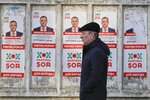 A man walks by electoral posters advertising the candidates of the the Show party, led by Israeli born Modovan businessman Ilan Shor, in Chisinau, Moldova, Thursday, Feb. 21, 2019, ahead of parliamentary elections taking place on Feb. 24. Moldova's president says the former Soviet republic needs good relations with Russia, amid uncertainty about the future of the European Union. (AP Photo/Vadim Ghirda)