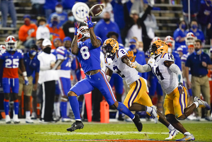 Florida wide receiver Trevon Grimes (8) makes a reception in front of LSU cornerback Dwight McGlothern (2) and safety Maurice Hampton Jr. (14) during the first half of an NCAA college football game Saturday, Dec. 12, 2020, in Gainesville, Fla. (AP Photo/John Raoux)