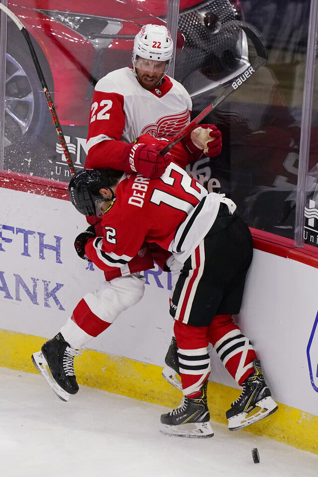 Detroit Red Wings left wing Patrik Nemeth, top, is checked by Chicago Blackhawks left wing Alex DeBrincat during the second period of an NHL hockey game in Chicago, Friday, Jan. 22, 2021. (AP Photo/Nam Y. Huh)
