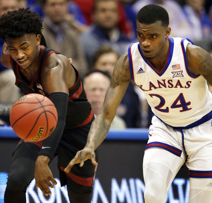 Stanford guard Daejon Davis, left, knocks the ball from Kansas guard Lagerald Vick (24) during the first half of an NCAA college basketball game in Lawrence, Kan., Saturday, Dec. 1, 2018. (AP Photo/Orlin Wagner)