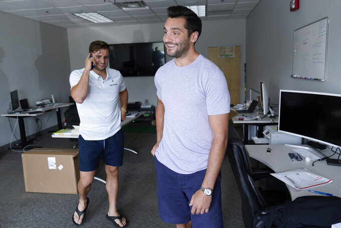 Former University of Michigan athletes Jared Wangler, left, and Niko Porikos, former Michigan athletes who have formed Valiant Management Group, work in Ann Arbor, Mich., on July 7, 2021. Valiant Management has agreements with 90 current Wolverines and has extended the opportunity to every player on the football team. (AP Photo/Paul Sancya)