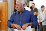 Portuguese Prime Minister and Socialist Party leader Antonio Costa picks up his ballot paper to vote at a poll station in Lisbon Sunday, Oct. 6, 2019. Portugal is holding a general election Sunday in which voters will choose members of the next Portuguese parliament. (AP Photo/Armando Franca)