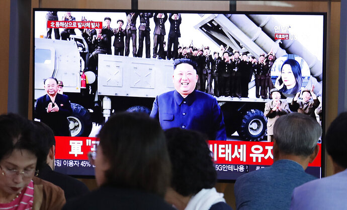 People watch a TV showing a file image of North Korean leader Kim Jong Un during a news program at the Seoul Railway Station in Seoul, South Korea, Wednesday, Oct. 2, 2019. North Korea on Wednesday fired projectiles toward its eastern sea, South Korea's military said, in an apparent display of its expanding military capabilities ahead of planned nuclear negotiations with the United States this weekend. (AP Photo/Ahn Young-joon)
