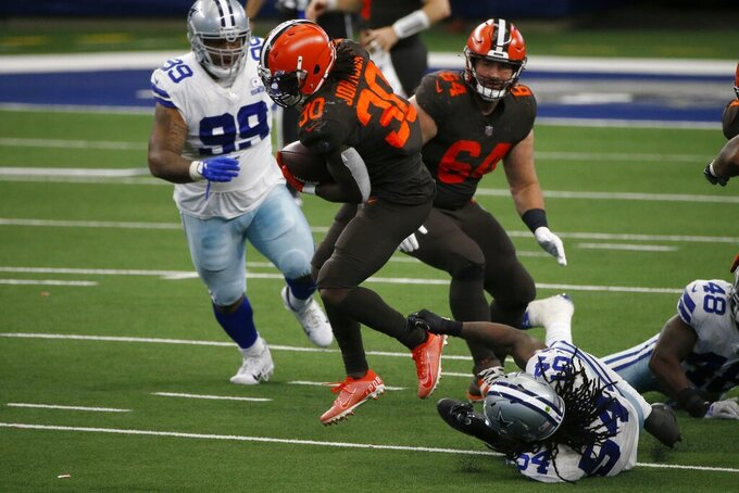 Cleveland Browns running back D'Ernest Johnson (30) attempts to break the grasp of Dallas Cowboys linebacker Jaylon Smith (54) after running the ball for a first down in the second half of an NFL football game in Arlington, Texas, Sunday, Oct. 4, 2020. The Cowboys' Antwaun Woods (99) and the Browns' JC Tretter (64) look on during the play. (AP Photo/Michael Ainsworth)