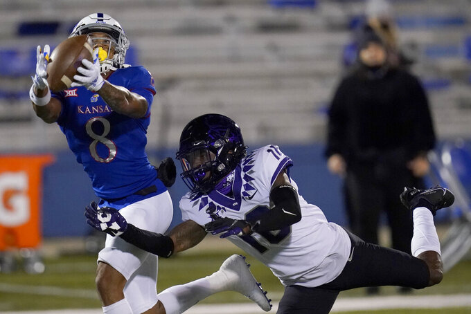 Kansas wide receiver Kwamie Lassiter II (8) catches a pass for a touchdown while defended by TCU cornerback C.J. Ceasar II (16) during the first half of an NCAA college football game in Lawrence, Kan., Saturday, Nov. 28, 2020. (AP Photo/Orlin Wagner)