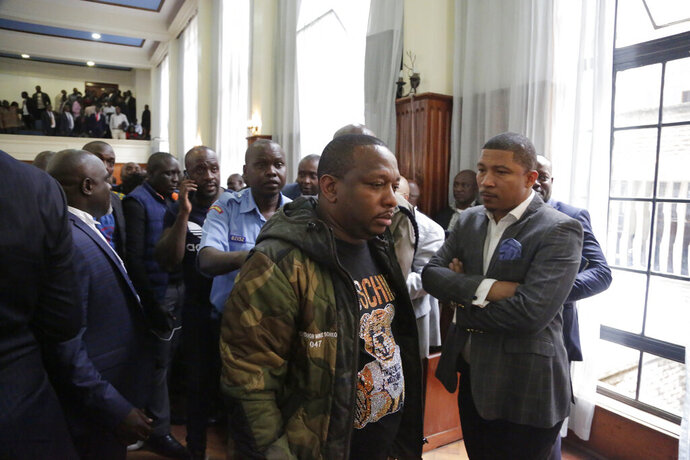 Nairobi governor Mike Gideon Mbuvi appears with other suspects accused of corruption, at the Mililani law court in Nairobi, Kenya, Monday Dec. 9, 2019. The flamboyant governor of Kenya's capital city, Nairobi, has been charged with 19 counts of graft-related charges as the country struggles to tackle runaway corruption. He denied the charges Monday, including embezzlement and money laundering. (AP Photo/Khalil Senosi)