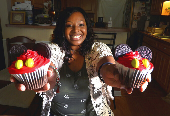 Gabrielle Williams of Columbus, Ga. holds two of her creations, cupcakes inspired by Mickey Mouse on July 9, 2021. She is the creator of the original Disney Movie Food Series on popular social media platform TikTok. (Mike Haskey/Ledger-Enquirer via AP)