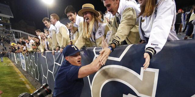 Georgia Tech coach Geoff Collins celebrates with fans after Georgia Tech defeated North Carolina State 28-26 in an NCAA college football game Thursday, Nov. 21, 2019, in Atlanta. (AP Photo/John Bazemore)