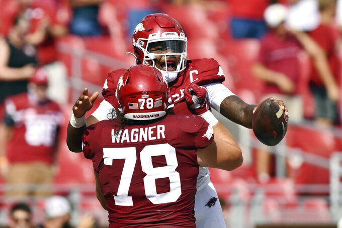 Arkansas quarterback KJ Jefferson (1) celebrates with teammate Dalton Wagner (78) during the first half of an NCAA college football game against Rice, Saturday, Sept. 4, 2021, in Fayetteville, Ark. (AP Photo/Michael Woods)
