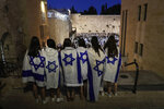 """Jewish ultranationalists covered with Israeli flag participate in the """"Flags March' next to the Western Wall, the holiest site where Jews can pray, in the Old City of Jerusalem, Tuesday, June 15, 2021. (AP Photo/Maya Alleruzzo)"""