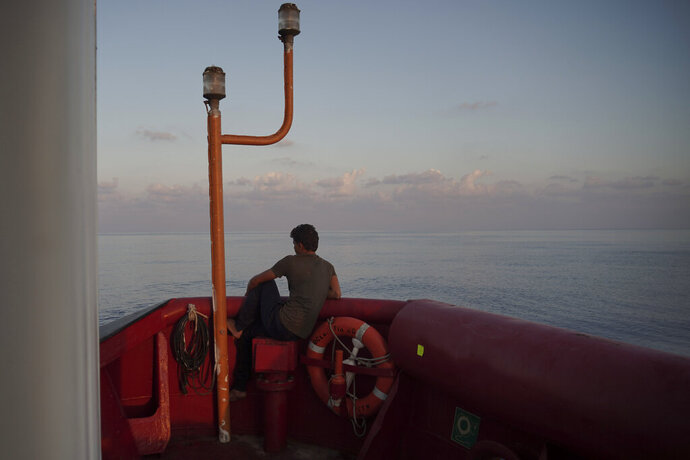 A rescued migrant from Egypt looks at the horizon from aboard the Ocean Viking in the Mediterranean Sea near the island of Lampedusa, Italy, Saturday, Sept. 14, 2019. Italy allowed a charity rescue ship to sail Saturday to a tiny southern island so the 82 migrants aboard could be transferred to shore, but the Italian foreign minister cautioned against interpreting the OK as a sign the new government is easing a crackdown on humanitarian vessels. (AP Photo/Renata Brito)