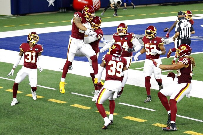 Washington Football Team's Montez Sweat, second from left, and Ryan Kerrigan (91) celebrate Sweat's interception of a pass by Dallas Cowboys' Andy Dalton that Sweat ran back for a touchdown during the second half of an NFL football game in Arlington, Texas, Thursday, Nov. 26, 2020. Kamren Curl (31), Jeremy Reaves (39), Daron Payne (94), Jon Bostic (53) and Chase Young (99) run to join the celebration. (AP Photo/Roger Steinman)