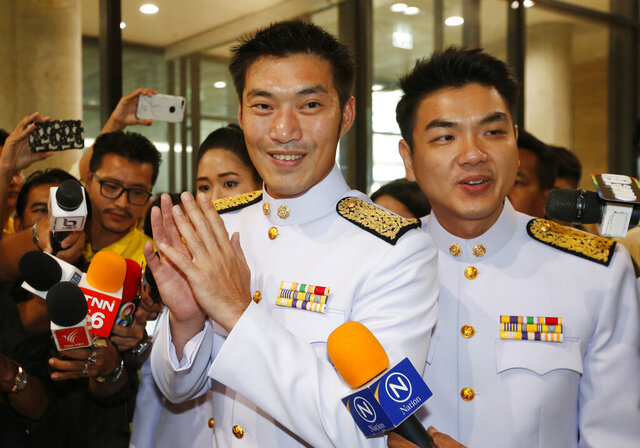FILE - In this May 24, 2019, file photo, the leader of the now dissolved Democrat Party's Thanathorn Juangroongruangkit, center, and secretary-general Piyabutr Saengkanokkul, right, arrive at the parliament in Bangkok, Thailand. Leaders of the former popular political party warned Wednesday that a reported plan to charge them with a crime could inflame the country's current political crisis. (AP Photo/Sakchai Lalit, File)