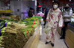 A woman wearing a mask and pajamas shop for vegetables at a store in Beijing, China on Tuesday, Feb. 18, 2020. On Monday, the Chinese Center for Disease Control and Prevention published a study of earlier cases of the disease, finding more than 80% of people infected had mild illness and the number of new infection seems to be falling since early this month. (AP Photo/Ng Han Guan)