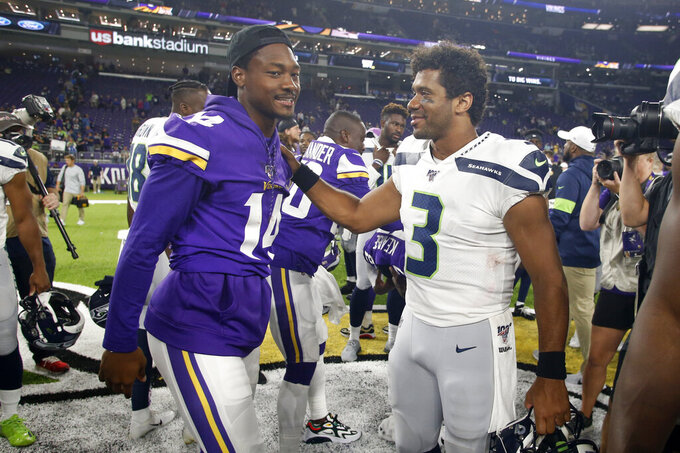 Minnesota Vikings wide receiver Stefon Diggs talks with Seattle Seahawks quarterback Russell Wilson (3) after an NFL preseason football game, Sunday, Aug. 18, 2019, in Minneapolis. The Vikings won 25-19. (AP Photo/Bruce Kluckhohn)