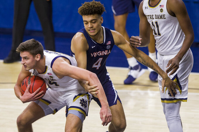 Notre Dame's Nate Laszewski (14) comes down with a rebound next to Virginia's Justin McKoy (4) and Notre Dame's Juwan Durham (11) during the first half of an NCAA college basketball game Wednesday, Dec. 30, 2020, in South Bend, Ind. (AP Photo/Robert Franklin)