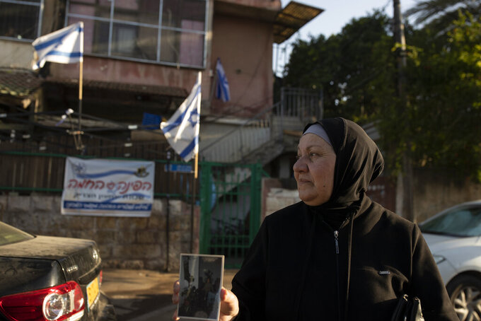Maryam Ghawi, a Palestinian, holds a family photo taken in the home behind her that is now occupied by Israeli settlers in the Sheikh Jarrah neighborhood of east Jerusalem, where hers is among dozens of Palestinian families facing imminent eviction from their homes by Israeli settlers, Tuesday, May 25, 2021.  After weeks of unrest that captured international attention, the evictions could still proceed. Some could be carried out in the coming months as international attention wanes, potentially setting off another round of bloodshed.(AP Photo/Maya Alleruzzo)