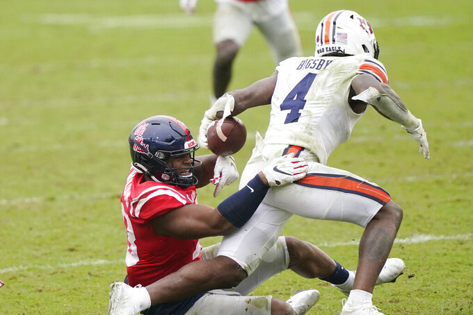 Auburn running back Tank Bigsby (4) runs through an attempted tackle by a Mississippi defender during the second half of an NCAA college football game in Oxford, Miss., Saturday, Oct. 24, 2020. (AP Photo/Rogelio V. Solis)