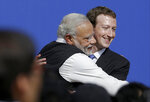 """FILE - In this Sept. 27, 2015, file photo, Facebook CEO Mark Zuckerberg, right, hugs Prime Minister of India Narendra Modi at Facebook in Menlo Park, Calif. Officials say a sweeping internet law, announced in February, that puts digital platforms like Twitter and Facebook under direct government oversight are needed to quell misinformation and hate speech and to give users more power to flag objectionable content. Critics of the law worry it may lead to outright censorship in a country where digital freedoms have been shrinking since Modi took office in 2014, many calling it """"digital authoritarianism."""" Facebook's WhatsApp, which has more than 500 million users in India, has sued the government, saying breaking encryption, which continues for now, would """"severely undermine the privacy of billions of people who communicate digitally."""" (AP Photo/Jeff Chiu, File)"""
