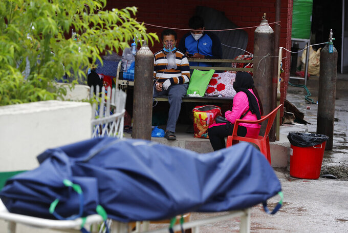 A patient receives oxygen as body of a COVID-19 patient lies covered on a stretcher outside an emergency ward of a government run hospital in Kathmandu, Nepal, Wednesday, May 12, 2021. (AP Photo/Niranjan Shrestha)