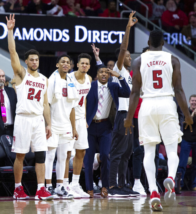 The North Carolina State bench reacts after North Carolina State's Eric Lockett (5) scores a three-pointer during the second half of an NCAA college basketball game against Pittsburgh in Raleigh, N.C., Saturday, Jan. 12, 2019. (AP Photo/Ben McKeown)