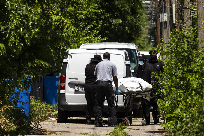 A crew removes one of four bodies from a house on South Morgan Street in Chicago's South Side on Tuesday, June 15, 2021. An argument in a house erupted into gunfire early Tuesday, police said. (Ashlee Rezin Garcia/Chicago Sun-Times via AP)