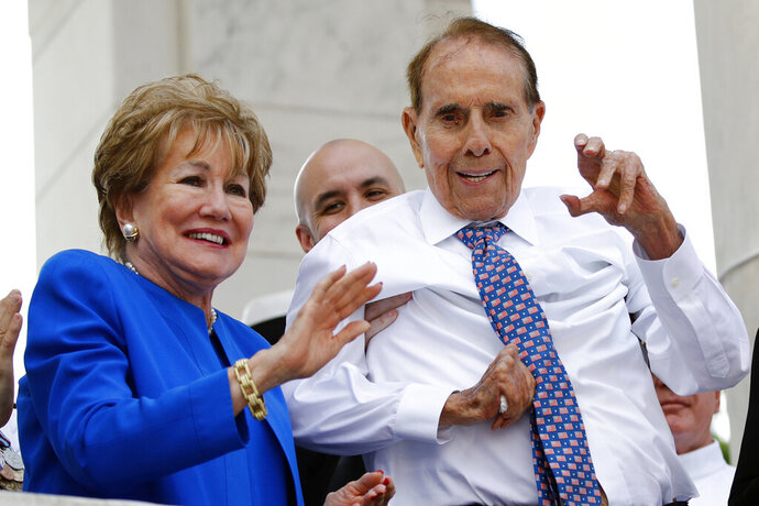 FILE - In this May 27, 2019 file photo, former Sen. Bob Dole, right, and his wife Elizabeth Dole acknowledge well-wishers during a Memorial Day ceremony, at Arlington National Cemetery in Arlington, Va. The political icon and 1996 Republican presidential nominee on Monday, Jan. 13, 2020, endorsed western Kansas' congressman Rep. Roger Marshall in the state's GOP Senate primary. Marshall's campaign announced Dole's backing and Dole tweeted that Marshall is